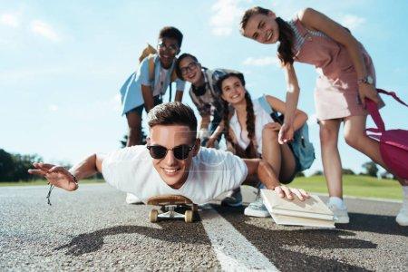 happy teenage multiethnic friends looking at smiling boy lying on skateboard in park