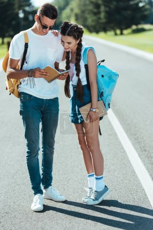 smiling teenage boy and girl with backpacks looking at notebook in park
