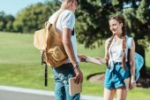 smiling teenage boy and girl holding book together in park