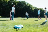multiethnic teenage classmates playing with soccer ball in park