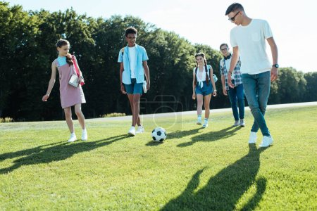 young multiethnic friends playing with soccer ball in park