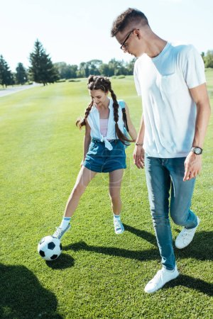 happy teenage boy and girl playing with soccer ball in park