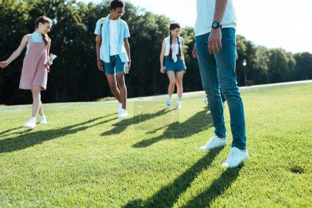 multiethnic teenage friends spending time on green meadow in park