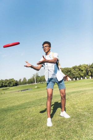 full length view of african american teenager with backpack playing with flying disc in park