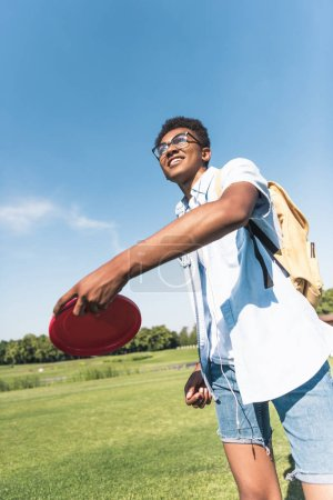 smiling african american teenager with backpack throwing flying disc in park