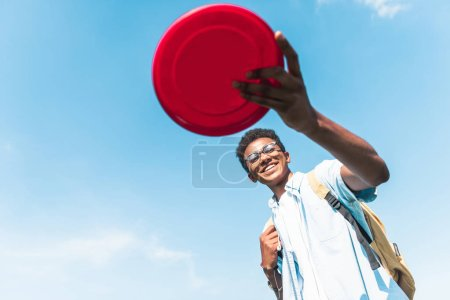 low angle view of happy african american teenager holding flying disc against blue sky