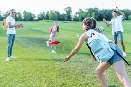 happy multiethnic teenage friends playing with flying disc in park