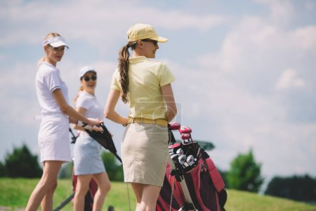 selective focus of female golfers with golf equipment walking at golf course