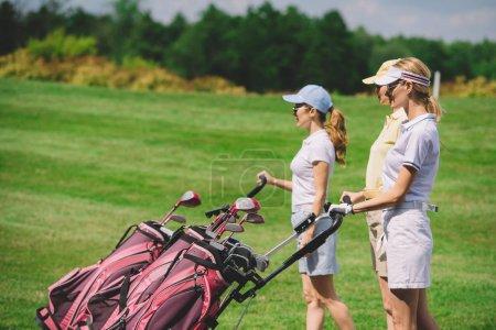 Photo pour Vue latérale des golfeuses avec équipement de golf marchant sur le terrain de golf - image libre de droit