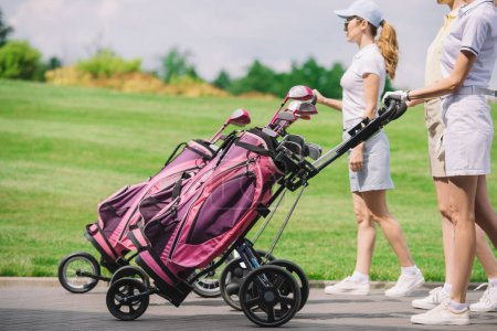 partial view of female golfers with golf equipment walking at golf course
