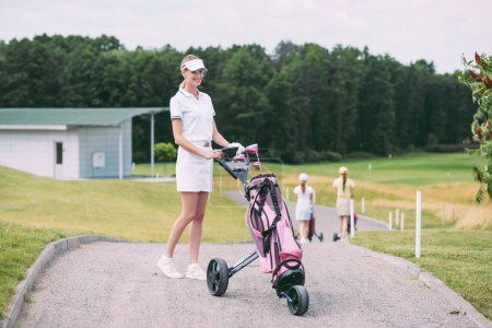 selective focus of cheerful female golf player in cap and white polo with golf gear at golf course