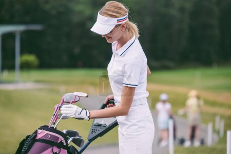 selective focus of female golf player in cap and white polo with golf gear at golf course