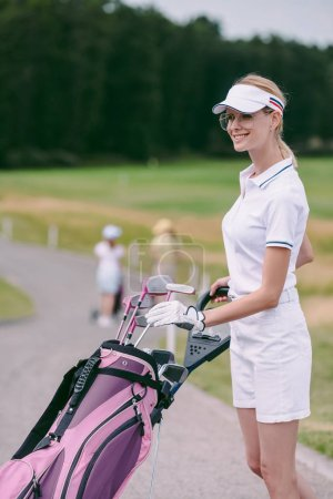 selective focus of smiling female golf player in cap and white polo with golf gear at golf course