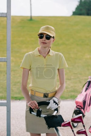 portrait of female golf player in cap and sunglasses standing near golf equipment at golf course