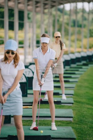 selective focus of focused female golfers playing golf at golf course