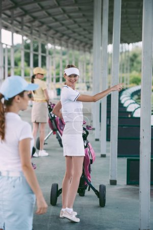 selective focus of woman with golf gear showing something to friend at golf course