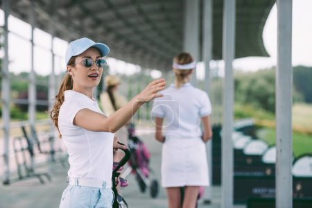 selective focus of woman in sunglasses with golf gear pointing away at golf course