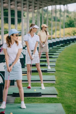selective focus of female golfers with golf clubs playing golf at golf course