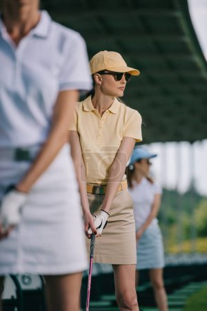 selective focus of woman in cap and sunglasses playing golf at golf course