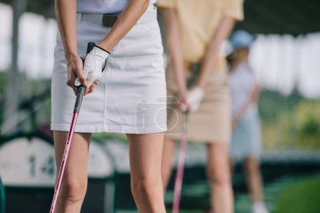 partial view of women playing golf at golf course