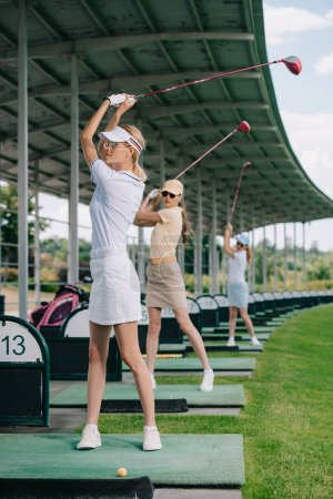 female golf player with golf clubs playing golf at golf course