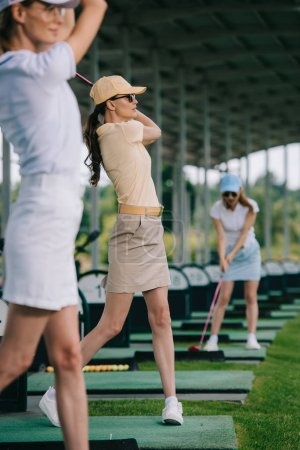 selective focus of women in caps playing golf at golf course
