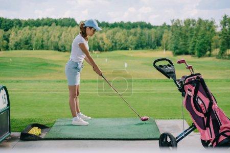 Photo pour Vue latérale de la femme en polo et casquette jouant au golf sur le terrain de golf - image libre de droit