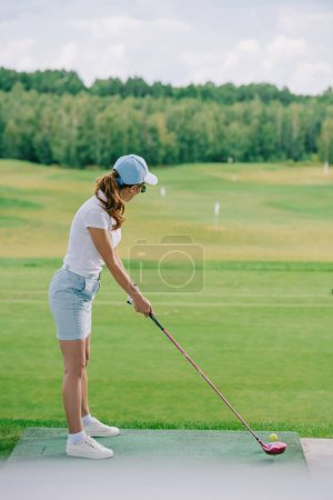 side view of woman in polo and cap playing golf at golf course