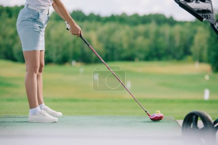 partial view of female player wit golf club standing at golf course on summer day