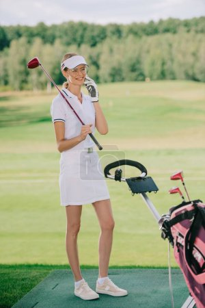 smiling female golf player in polo and cap with golf club in hand talking on smartphone at golf course