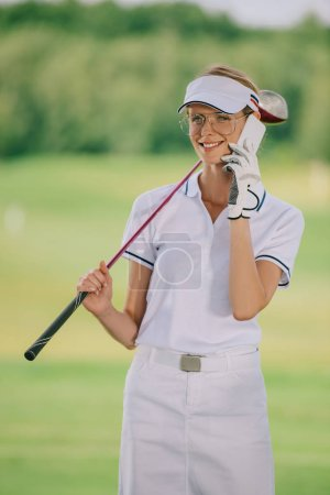 portrait of smiling female golf player in polo and cap with golf club in hand talking on smartphone at golf course