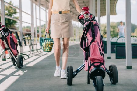 cropped shot of woman with golf gear walking at golf course
