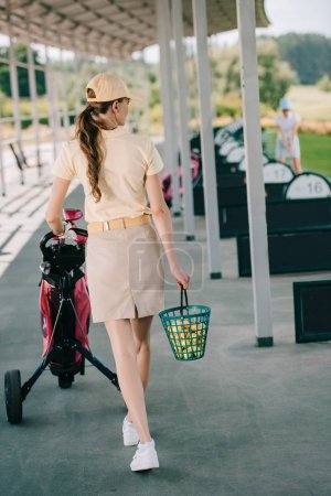 back view of woman in polo and cap with golf gear walking at golf course