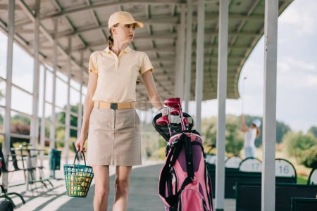 portrait of woman in polo and cap with golf gear walking at golf course