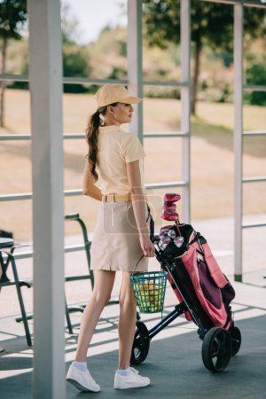 side view of attractive woman in polo and cap carrying golf equipment at golf course