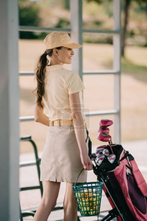 side view of smiling woman in polo and cap carrying golf equipment at golf course