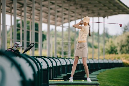 woman in yellow cap and polo playing golf at golf course