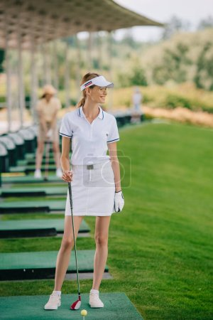 selective focus of smiling female golfer in polo and cap with golf club looking away at golf course