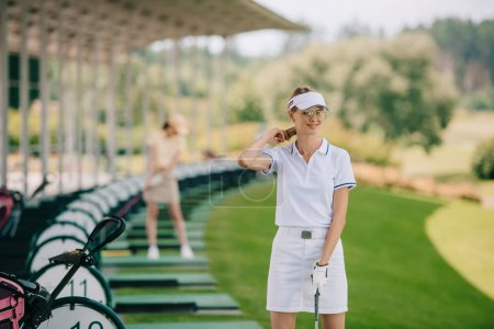 selective focus of smiling female golfer in polo and cap with golf club at golf course