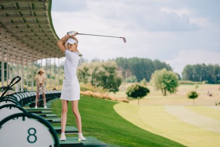 selective focus of smiling female golfer in polo and cap playing golf at golf course