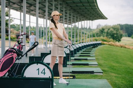 pensive female golfer in polo and cap with golf club looking away at golf course