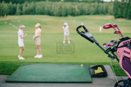 selective focus of golf gear and women in caps at golf course