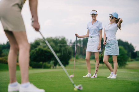 selective focus of smiling women in caps with golf equipment looking at friend playing golf at golf course