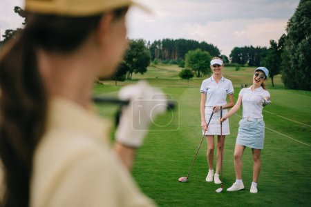 selective focus of smiling women with golf clubs at golf course