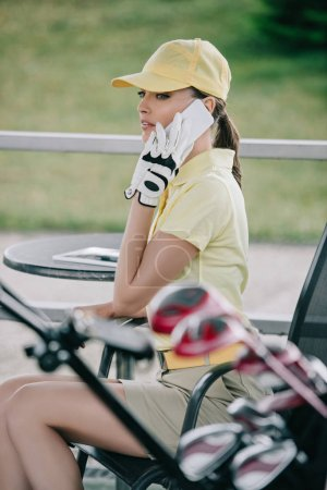 side view of woman in cap, polo and golf glove talking on smartphone at golf course