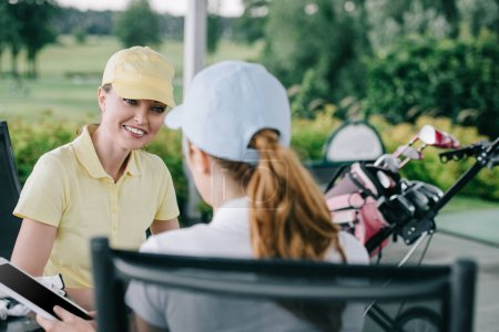 business partners with tablet discussing work after golf game at golf course