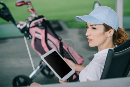 side view of pensive female golf player with tablet in hands at golf course