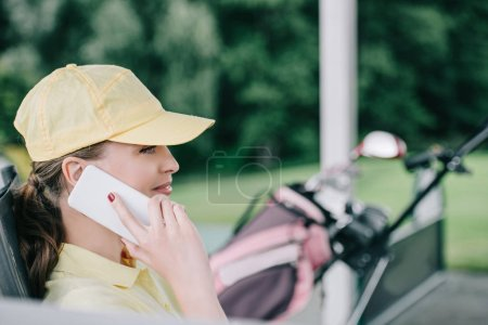 side view of female golf player in cap talking on smartphone at golf course