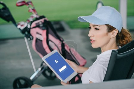 side view of female golf player with tablet with facebook logo on screen in hands at golf course