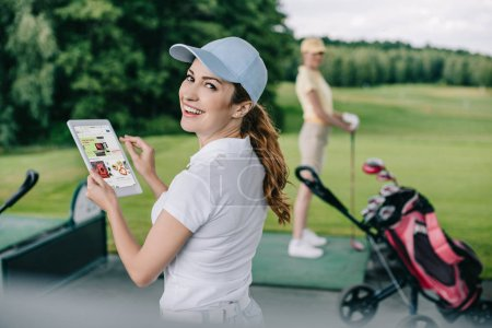 selective focus of smiling woman holding tablet with ebay logo and friend playing golf behind at golf course